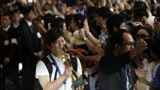 Pemain Jepang Miho Fukumoto membawa trophy Piala Dunia saat mendarat di Tokyo