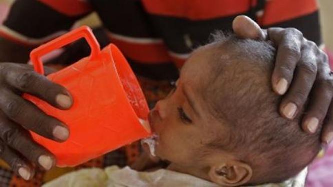 Seorang ayah Somalia menyuapi susu anaknya di kamp pengungsian di Kenya.
