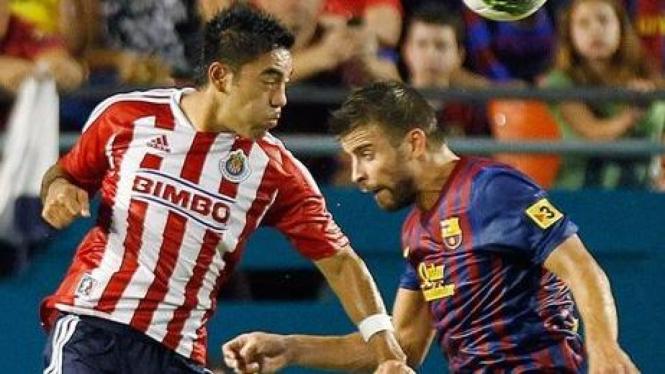 Duel pemain Chivas, Marco Fabian (kiri) dan bek Barcelona, Gerard Pique