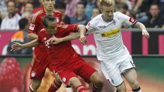Pemain Munich Rafinha (merah) dan pemain Moenchengladbach Marco Reus