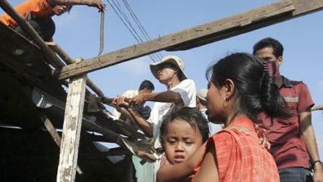 Warga sekitar danau Boeung Kak, Kamboja, menyaksikan rumahnya dirobohkan.