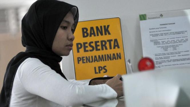 Seorang nasabah melakukan transaksi di bank peserta penjaminan LPS.