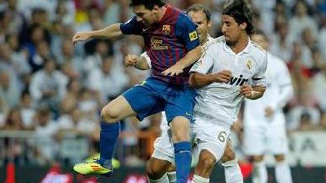 Sami Khedira (kanan) berduel dengan Lionel Messi (kiri)