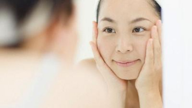 wanita membersihkan wajah