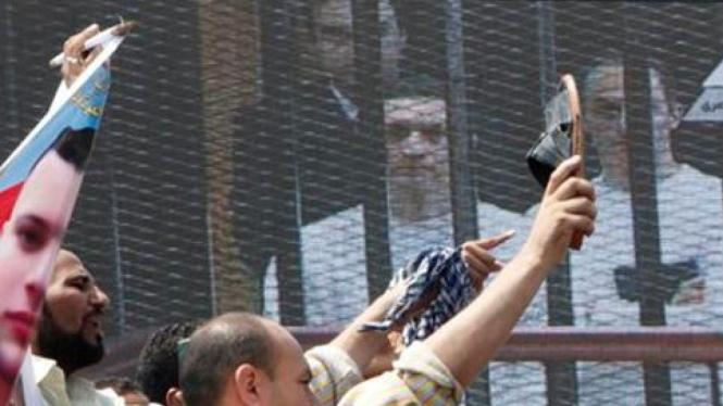 Warga menyaksikan jalannya pengadilan Mubarak melalui layar besar.