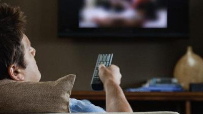 Pria menonton televisi.