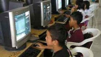 Anak-anak bermain game online di PC.