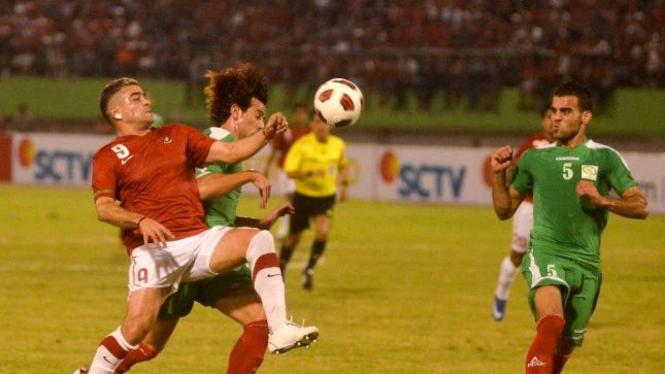 Cristian Gonzales (kiri/merah) berusaha melewati pemain Palestina