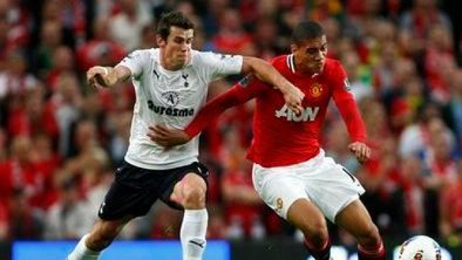 Gareth Bale (Tottenham/kiri) berusaha melewati Chris Smalling (MU)