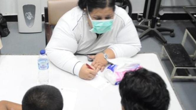 dr Aisha Wardhana saat memeriksa TKI yang dipulangkan Malaysia