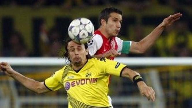 Pemain Arsenal Robin Van Persie (belakang) dan pemain Dortmund Neven Subotic