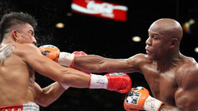 Floyd Mayweather Jr (kanan) memukul Victor Ortiz