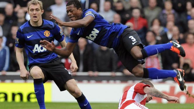 Pemain MU Patrice Evra (biru-hitam) dan pemain Stoke City