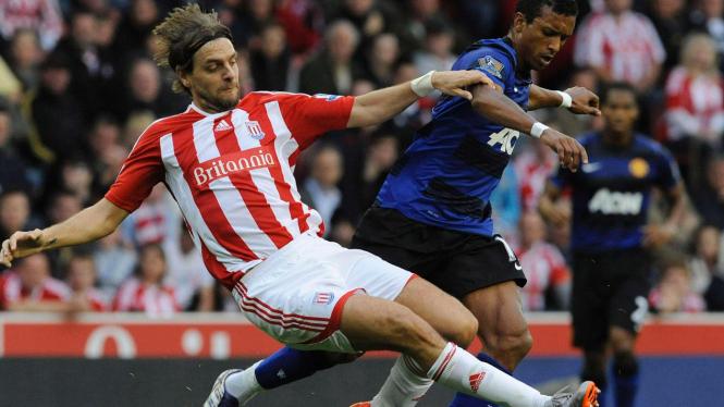 Pemain MU Nani (hitam-biru) dengan pemain Stoke City Jonathan Woodgate