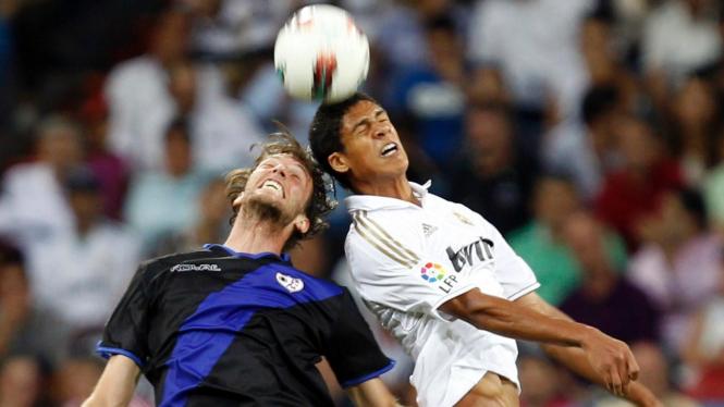 Pemain Real Madrid Raphael Varane (putih) dengan pemain Vallecano Miguel Perez