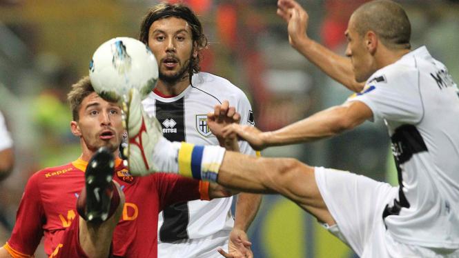Pemain As Roma Fabio Borini (merah) berduel dengan pemain Parma