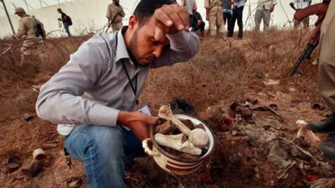 Warga menggali tulang pada lokasi yang diduga kuburan massal di Tripoli, Libya