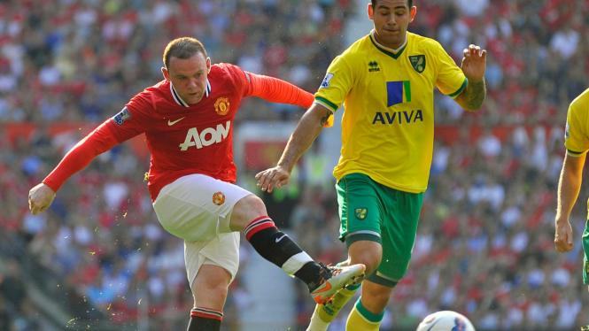 Pemain MU Wayne Rooney (merah) dan pemain Norwich City Bradley Johnson