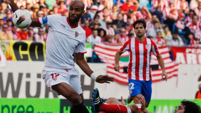 Pemain Sevilla Frederic Kanoute (putih) dan pemain Atletico Madrid