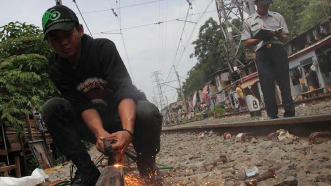 Petugas Memperbaiki Rel Kereta Api Yang Patah