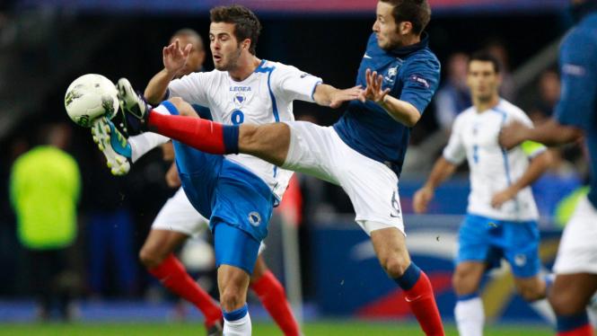 Pemain Prancis Yohan Cabaye (biru) di pertandingan melawan Bosnia