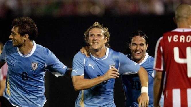 Striker Uruguay, Diego Forlan (tengah), usai membobol gawang Paraguay