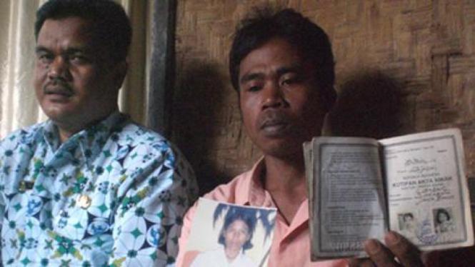 Iya Iskandar, memegang foto istrinya, Tini, yang meninggal di Malaysia.