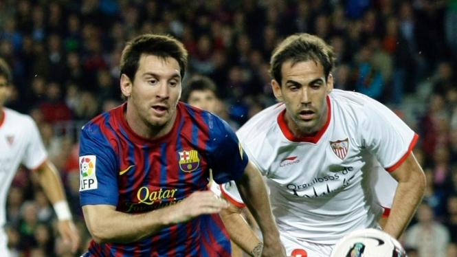 Pemain Barca Lionel Messi berduel dengan Fernando Navarro