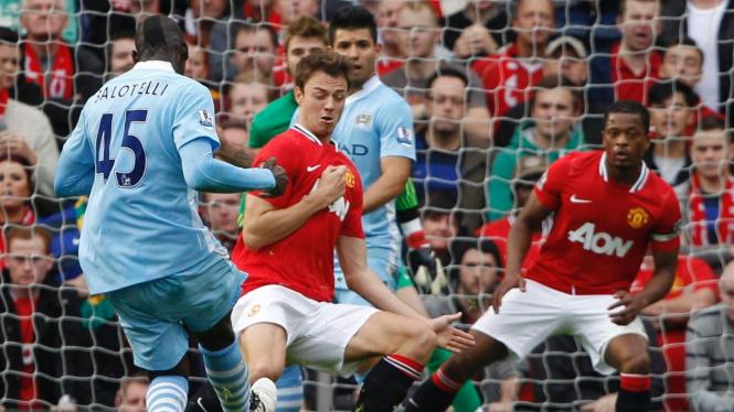 Pemain Manchester United (merah) berduel dengan pemain City