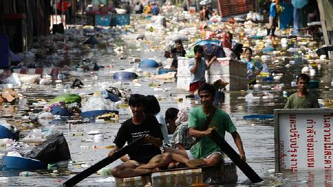 Korban banjir mengayuh di antara sampah