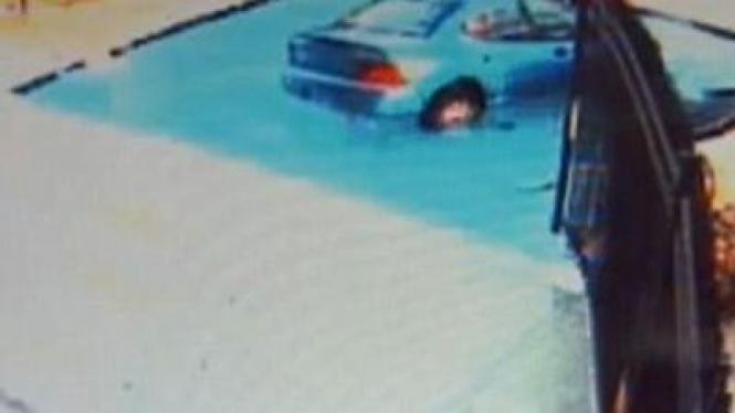 Sebuah mobil sedan terjun ke kolam renang apartemen