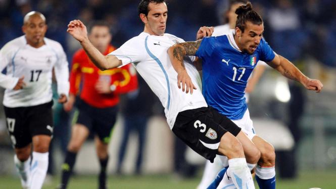 Pemain Italia Pablo Daniel Osvaldo (biru) dan pemain Uruguay Diego Godin