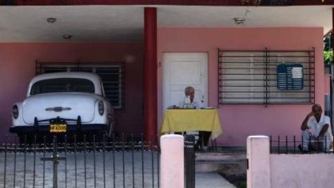 Penjual kopi berlisensi di depan rumahnya di Havana, Kuba
