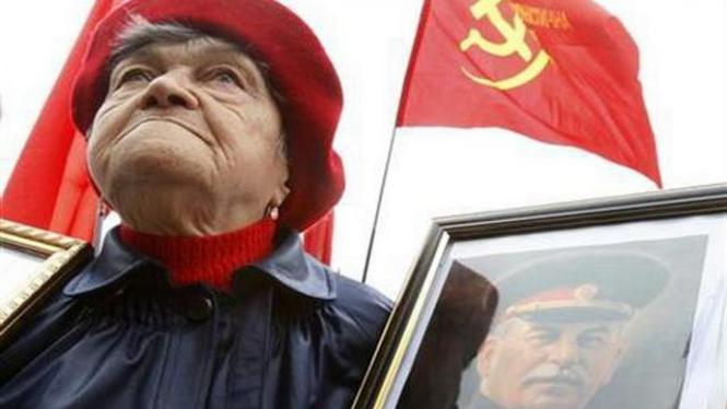 Seorang perempuan tua memegang foto Josef Stalin