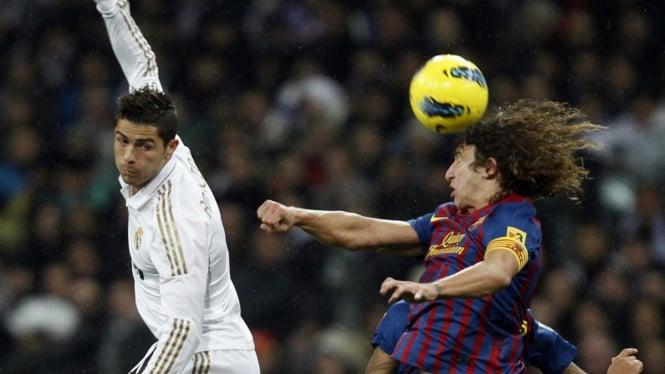 Cristiano Ronaldo (putih) berduel dengan Carles Puyol dalam laga El Clasico