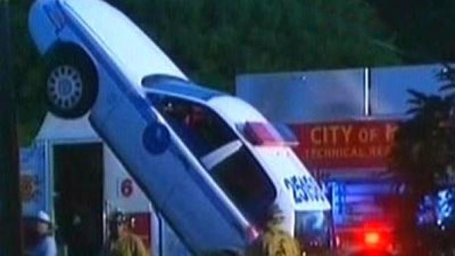 Mobil Polisi Tersangkut pada Tiang Listrik