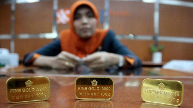 Pegawai Memperlihatkan Emas Batangan di Bank BNI Syariah