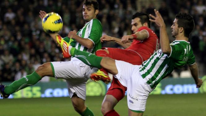 Pemain Sevilla, Alvaro Negredo (tengah) berduel dengan pemain Real Betis