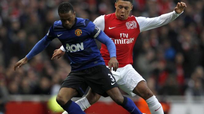 Patrice Evra (kiri) berduel dengan Oxlade-Chamberlain saat Arsenal jumpa MU