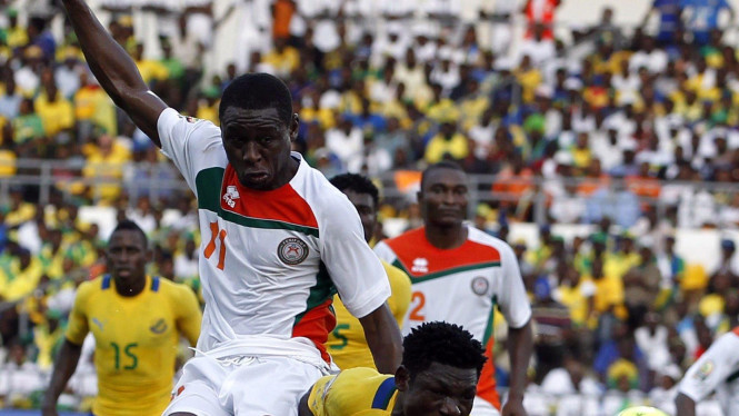 Pemain Gabon, Mouele Edmond (bawah) berduel dengan pemain Niger