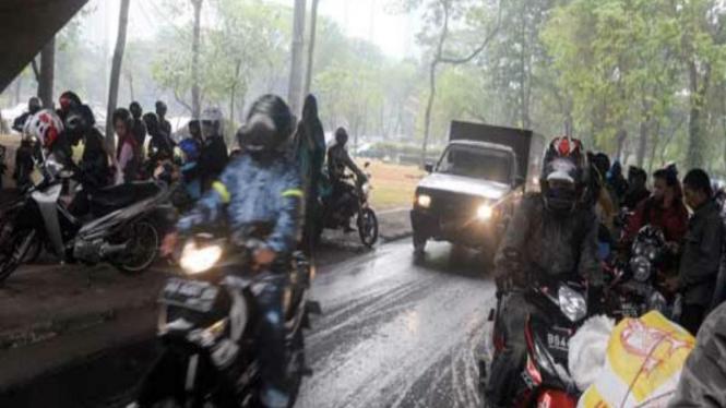 Pengendara Motor yang Berteduh Saat Hujan