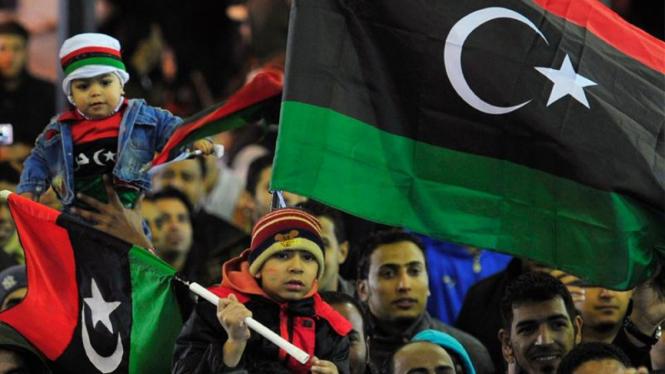 Rakyat Libya mengibarkan bendera nasional.