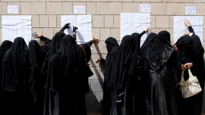 Warga Sanaa, Yaman, mencari nama mereka di daftar pemilih