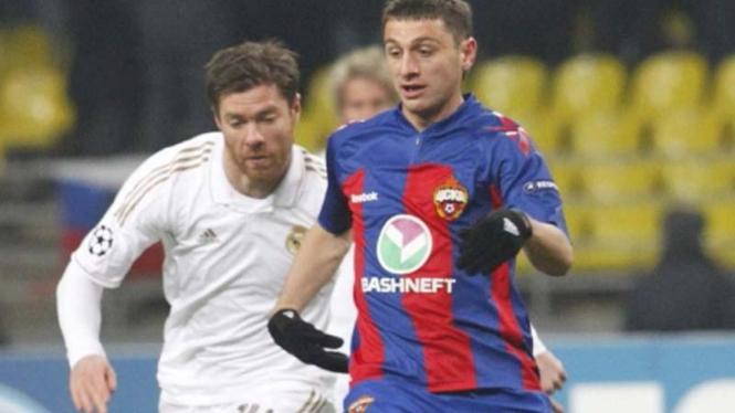 Xabi Alonso (kiri) menghadang pemain CSKA