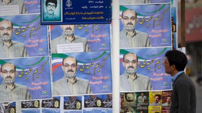 Seorang pria di Teheran melihat spanduk kandidat anggota parlemen