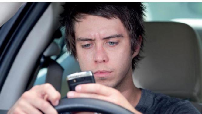 Mengemudi mobil sambil menggunakan smartphone untuk jejaring sosial