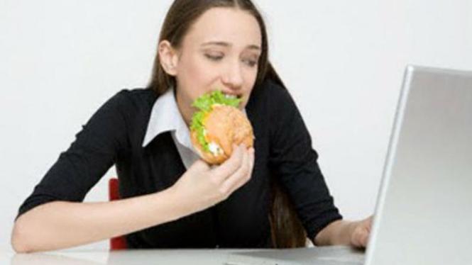 Seorang wanita menyantap makanan