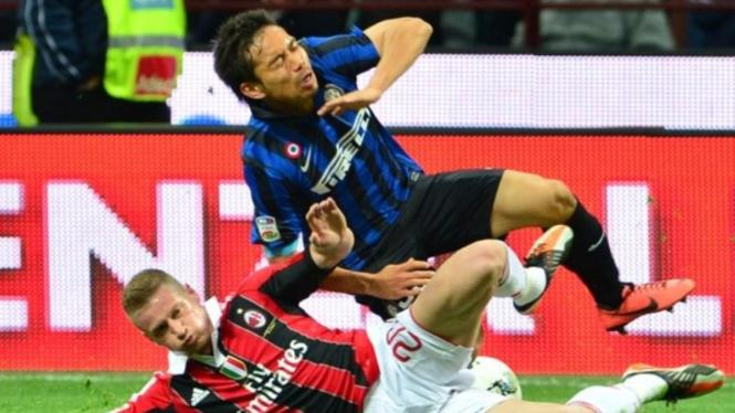 Bek AC Milan, Ignazio Abate (bawah), saat menekel Yuto Nagatomo