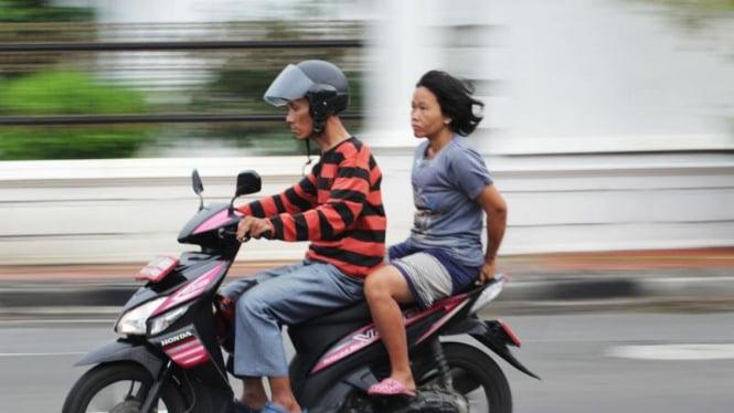 Pengendara memboncengi penumpang tanpa helm.