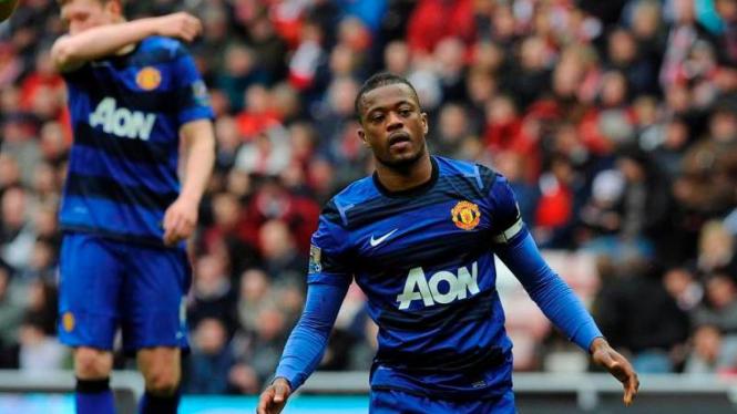 Kapten Manchester United, Patrice Evra, bertekuk lutut usai laga.